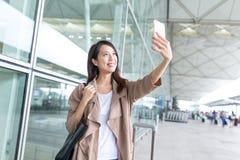 Femme prenant le selfie par le téléphone portable dans l'international a de Hong Kong Images libres de droits