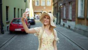 Femme prenant le selfie sur la rue Jeune femme gaie marchant sur la vieille rue européenne de ville et prenant le selfie avec clips vidéos