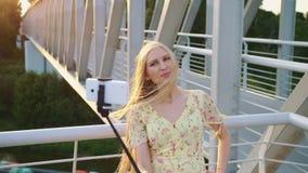Femme prenant le selfie sur le pont Femme assez blonde gaie se tenant sur le pont piétonnier et prenant le selfie avec le monopod banque de vidéos