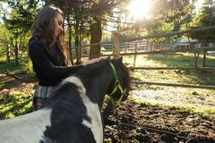 Femme prenant le soin au-dessus du poney noir avec de longs cheveux dans le domaine Photo libre de droits