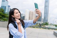 Femme prenant le téléphone portable de selfie avec le geste i de doigt d'amour Images stock