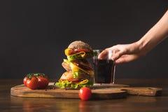 Femme prenant le verre de kola de table avec le grand sandwich savoureux Images stock