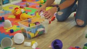 Femme prenant les jouets en bois dans la poubelle en plastique banque de vidéos