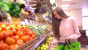 Femme prenant les pommes vertes de la boîte sur la stalle de fruit dans le supermarché clips vidéos