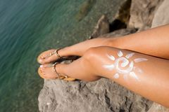 Femme prenant un bain de soleil sur la plage avec un dessin du soleil sur sa jambe Image stock