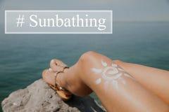 Femme prenant un bain de soleil sur la plage avec un dessin du soleil sur sa jambe Photographie stock