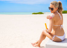 Femme prenant un bain de soleil sur la plage et appliquant la crème de protection du soleil Photos libres de droits