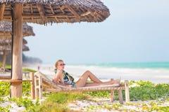 Femme prenant un bain de soleil sur la plage tropicale Image libre de droits