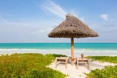 Femme prenant un bain de soleil sur la plage tropicale Photo stock