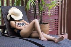 Femme prenant un bain de soleil sur le canapé Image libre de droits