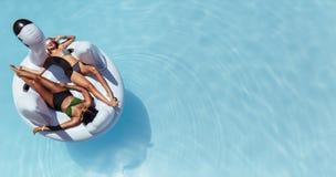 Femme prenant un bain de soleil sur le jouet gonflable de flottement de piscine Photographie stock