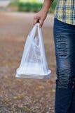 Femme prenant un sachet en plastique du déjeuner emballé Image stock