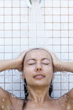 Femme prenant une douche Photos libres de droits