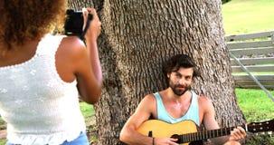 Femme prenant une photo d'un homme jouant la guitare banque de vidéos
