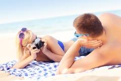 Femme prenant une photo de son ami à la plage Image libre de droits