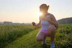 Femme prenant une photographie de téléphone portable sur un chemin de gravier au coucher du soleil Photographie stock libre de droits
