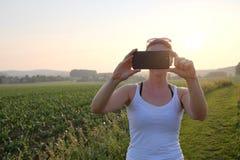Femme prenant une photographie de téléphone portable sur un chemin de gravier au coucher du soleil Photos libres de droits