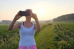 Femme prenant une photographie de téléphone portable sur un chemin de gravier au coucher du soleil Images stock