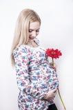Femme prgnant de sourire avec la fleur Photo stock