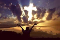 Femme priant à un dieu avec le rayon de la lumière formant la croix sur le ciel Photos stock