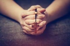 Femme priant avec un rosaire images stock