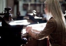 Femme priant dans l'église Photographie stock