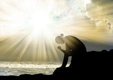 Femme priant à un dieu au coucher du soleil Image stock
