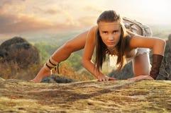 Femme primitive sur une roche au coucher du soleil Femme d'Amazone photographie stock libre de droits
