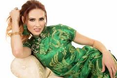 Femme principale rouge dans la robe asiatique étroite sur le sofa Image libre de droits