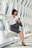 Femme professionnelle de sourire d'affaires attendant avec le téléphone intelligent Photos libres de droits