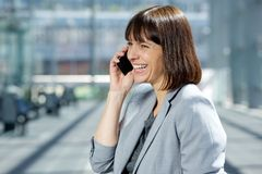 Femme professionnelle heureuse d'affaires à l'aide du téléphone portable image stock