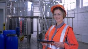 Femme puissante à l'usine, portrait de femelle d'ingénieur dans le casque antichoc et combinaisons avec la fabrication de comprim banque de vidéos