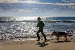 Femme pulsant au bord de la mer avec son chien Image libre de droits