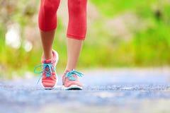 Femme pulsante avec les jambes sportives et les chaussures de course Photo libre de droits