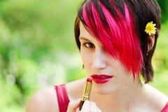 Femme punke appliquant le rouge à lievres Photographie stock libre de droits