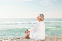 Femme qui s'assied sur la plage Images libres de droits