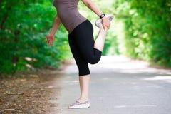 Femme réchauffant avant de pulser, exercice extérieur images libres de droits