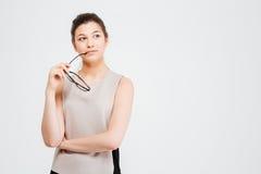 Femme réfléchie attirante d'affaires tenant des verres et la pensée photos stock