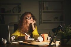 Femme réfléchie aux notes d'écriture de travail Photographie stock libre de droits
