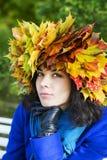 Femme réfléchie avec des feuilles d'érable sur la tête Image stock