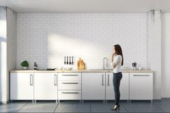 Femme réfléchie dans la cuisine blanche Image stock
