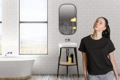 Femme réfléchie dans la salle de bains Photos stock