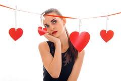 Femme réfléchie de brune dans l'amour posant avec le coeur rouge sur le fond d'isolement sur le fond blanc Image stock