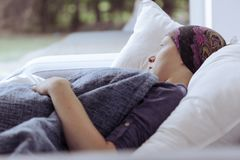 Femme réfléchie luttant avec le lupus regardant hors de l'hospice de fenêtre à la maison photographie stock