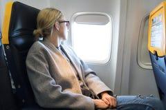 Femme réfléchie regardant par la fenêtre tout en voyageant en avion images libres de droits
