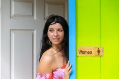 Femme réfléchie se penchant contre une porte de toilettes image libre de droits