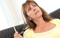 Femme réfléchie tenant ses verres Image stock
