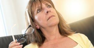 Femme réfléchie tenant ses verres, effet de la lumière Image libre de droits