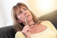 Femme réfléchie tenant ses verres, effet de la lumière Photos libres de droits