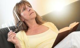 Femme réfléchie tenant ses verres et lisant un livre, effet de la lumière Photo libre de droits